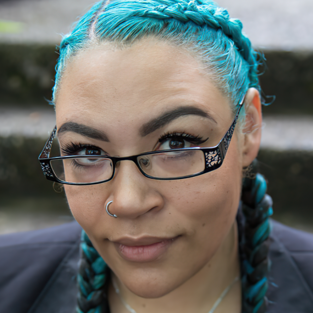 Close-up portrait photography of Sherae Lascelles with glass, blue-dyed hair in braids, glasses, and nose ring, lowing upward at camera.